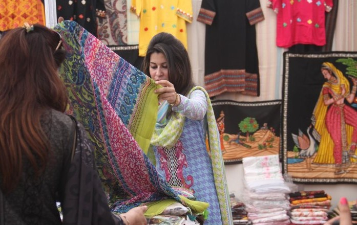 Woman takes interest in dresses displayed during Islamabad Expo organized by Islamabad Women Chamber of Commerce and Industries at Jinnah Convention Center.