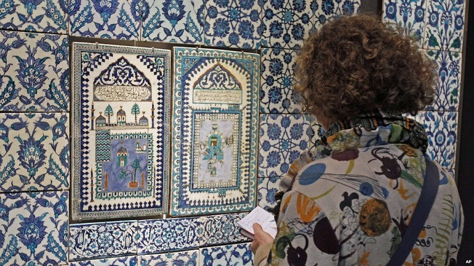 A member of the media takes notes beside a ceramic tile display in the Louvre's new Islamic Art section. Photo: AP